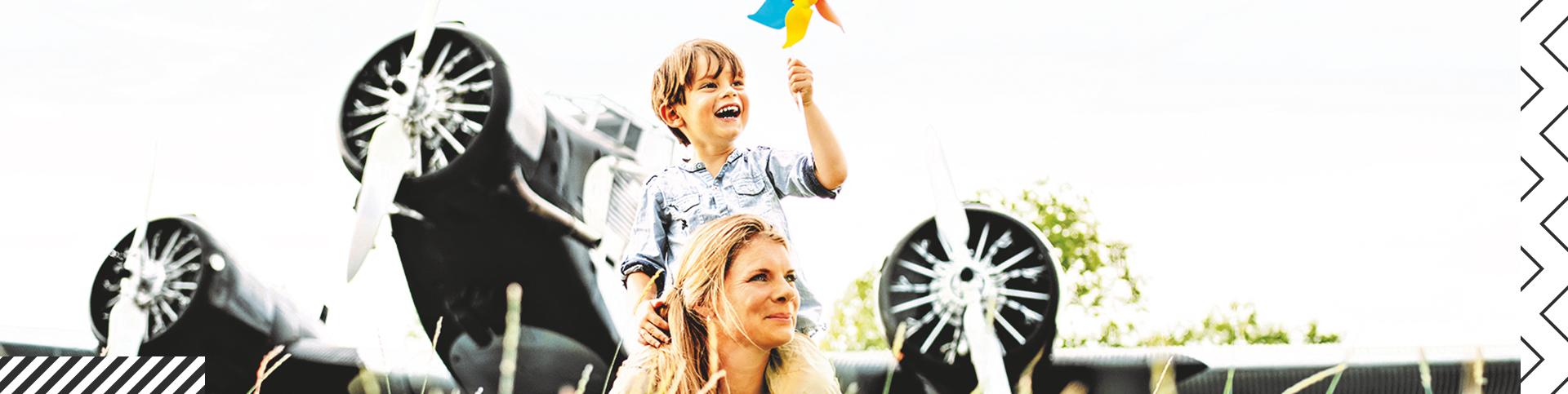 Eine Mutter mit ihrem Sohn vor einem Flugzeug, beide lachen glücklich