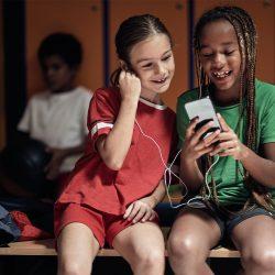 2 Kinder in Fußballtrikots schauen sich die FC Bayern München Kinder-App an